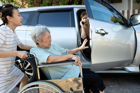 Asian female people enjoy talking on the phone,opening the door car slamming the leg of elderly feel pain,inattentive girl crashed into leg of disabled senior woman in wheelchair while open the door
