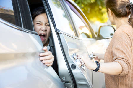 Accident,hand slammed the door,mischievous child girl was pinched her hand or fingers in the car door,asian daughter shouted in pain,woman or mother closed the car door without careful,inadvertently 版權商用圖片