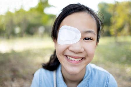 Fröhliche asiatische Kindermädchenabdeckung mit verbundenen Augen nach einer Operation oder Behandlung von Strabismus, faules Auge, hygienisch, Infektionsschutz, Staubschutz, lächelnde weibliche Menschen, die Schmerzen verspüren, Augenverletzungen