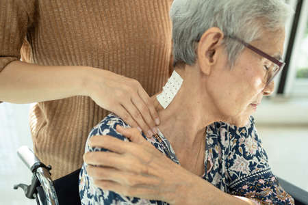 Asian senior mother have nerve pain,shoulder ache,neck pains,female caregiver or daughter massaging her shoulders, frustrated elderly woman,feeling exhausted,neck painful,muscle soreness,inflammation