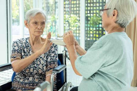 Unglückliche asiatische Seniorin, die ablehnt, Geste Hand NEIN, müde alte Menschen, die sich krank fühlen, Dysphagie, Dyspepsie oder gelangweilt vom Essen, Freund, der ältere Patienten im Rollstuhl füttert, Appetitlosigkeit, Anorexie-Konzept Standard-Bild