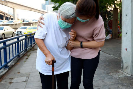 Tired senior woman wearing hygienic mask walk outdoor on street sidewalk in city,feel sick,vertigo,nauseous,allergy to dust,pollution,smog,PM2.5,air contamination,elderly people inhaling toxic fumes