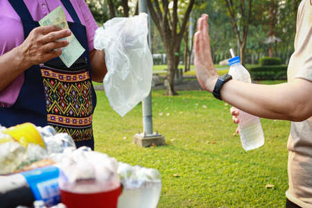 """Asian young woman rejecting and trying to reduce the use of plastic bags,campaign to stop plastic pollution,say no to plastic bags from the female street vendor,gesture hand""""NO""""save the world concept"""