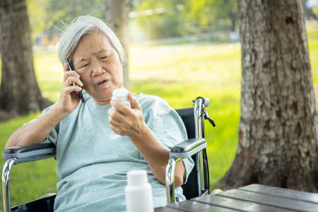 Sick asian senior woman holding bottle of medicine,calling doctor requesting information,worried female elderly consulting,asking with pharmacist about pill,medical consultation service of hospital