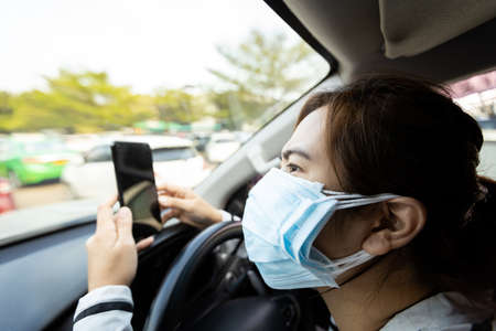 Anxiety asian woman with allergic rhinitis,severe dust allergy wearing protection face mask of many layers,check the amount of dust or search for news from the phone,worried about air pollution,PM2.5