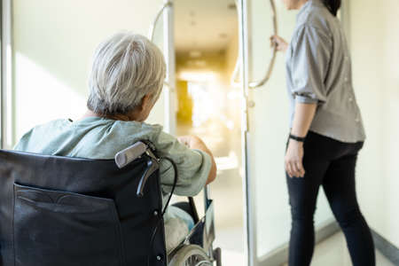 Stressed asian senior woman sit in wheelchair peeking out the door at hospital corridor,elderly patient feel afraid ,anxious to the treatment or undergoing knee surgery,worried about health problems