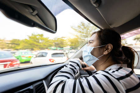 Asian woman driving with a medical face mask on.