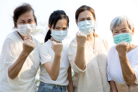 Group of people wearing medical mask to prevent infection from spreading of Covid-19,asian family raised a fists and prepare for the epidemic crisis or fight the Coronavirus,concept of encouragement