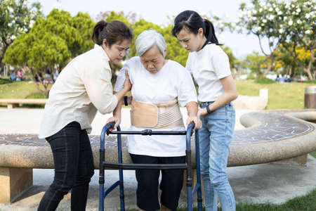 Asian elderly use walker during rehabilitation for safety after knee surgery,daughter,granddaughter help,care,support her senior mother while stand up to practice walking for exercise,physical therapy