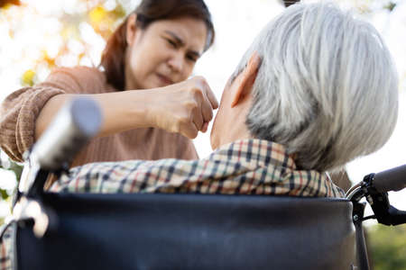 Senior mother who is threatened by daughter,Angry woman get mad with raises her fist and punching on the face of elderly people,aggression,ungratefulness,victim of domestic violence and abuse concept