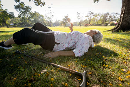 Senior woman was lying on the ground because slipped down and fell,walking alone at park,elderly is trying to raise their hand and ask for help,old people fell to the floor during exercise,health care Archivio Fotografico