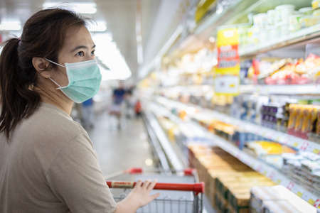 Asian woman wear a mask,looking fresh water and milk,choosing necessary food products,people panic buying and hoarding during the Covid-19,Coronavirus epidemic,girl preparing for pandemic quarantine