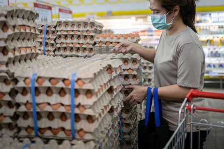 Asian woman wearing face mask,choosing fresh chicken eggs while shopping food,people panic buying and  hoarding during the Covid-19, Coronavirus epidemic.girl preparing for pathogen virus pandemic
