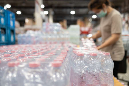 Lot of plastic packaging of fresh water,people wearing face mask,choosing fresh water,beverage and food,woman panic buying and hoarding during the Covid-19,Coronavirus epidemic,preparing for pandemic