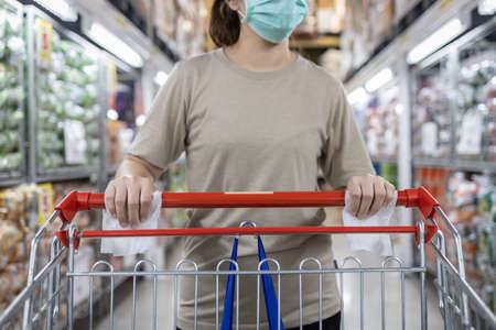 Woman wear protective mask with shopping cart,trolley,hand of girl using tissue paper to touch objects instead of hands to avoid contamination,outbreak of Covid-19,during the pandemic of Coronavirus