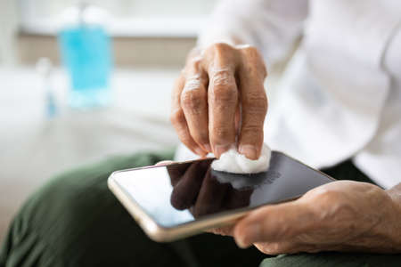 Hands of elderly people using cotton wool with alcohol to wipe on mobile phone to avoid contamination of Coronavirus,prevent contagious disease of Covid-19 virus,cleaning phone to eliminate of germs