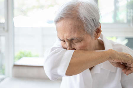 Asian elderly people sneezing,coughing into her sleeve or elbow to prevent spread Covid-19,Corona virus,sick senior woman has flu,fever covering nose,mouth with her arm from dust,air pollution,allergy