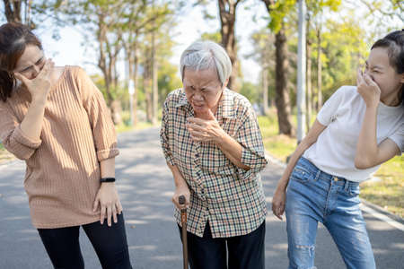 Sick senior woman has sneeze,allergic to weather,spreading germs with sneezing,contagious disease of influenza with a contaminated patient,symptoms of cold,seasonal flu pandemic,respiratory infection