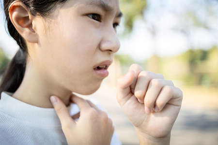Sick asian woman has a chronic cough with tonsillitis,ill child girl touch the neck with fever,acute cough,sore throat pain irritation,voice is hoarse from cold,influenza, respiratory tract infection