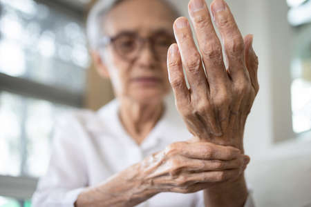 Elderly female patient suffer from numbing pain in hand,numbness fingertip,arthritis inflammation,beriberi or peripheral neuropathies,senior woman massage her hand with wrist pain,rheumatoid arthritis