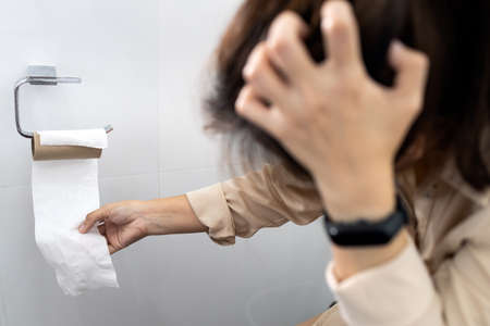 Stressed woman sitting on toilet bowl with tissue roll that was about to run out,effects from the Coronavirus,problem of tissue paper is out of stock during outbreak of Covid-19,out of toilet paper