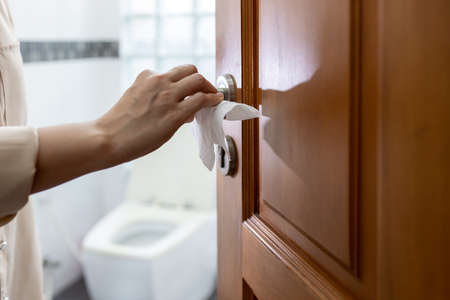 Hand with door handle,girl open the bathroom door,woman using tissue paper to touch the door knob instead of hands to prevent infection of Covid-19,outbreak of Coronavirus,pandemic,contagious diseases Archivio Fotografico