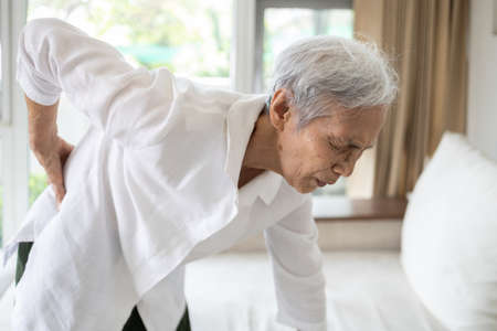 Sad asian senior woman with back and hip joint painful while standing up,female patient having backache,lumbago pain,hand touch on the hip,elderly suffer from ribs hurt or waist pain,health problems