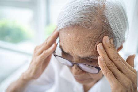Sick senior woman with headache,pain in the head,brain system problems,chronic illness,elderly has dizziness,symptoms of benign paroxysmal positional vertigo,meniere's disease or fatigue,lack of sleep