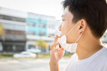 Homme asiatique avec un masque de protection pendant la pandémie de Covid-19, tient une cigarette dans sa bouche, fumeurs masculins fumant, propagation du coronavirus avec des gouttelettes sortant de la fumée de cigarette, maladies aéroportées