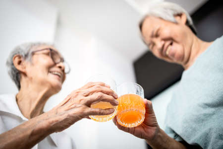 Healthy elderly sibling drinking vitamin C,orange juice and clinking glasses at home,senior people with effervescent vitamin C,strengthening the immunity for cold,flu,prevent the Coronavirus,Covid-19