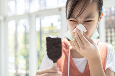 Sick asian child girl has runny nose and blows her nose into a tissue paper while eating too much ice cream,woman with illness from colds,sneeze,influenza,symptoms of infection,respiratory problems