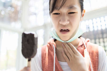 Sick asian child girl with a flu,dry cough and a sore throat,eating too much ice cream,loss of taste and sense of tasting food or illness from Coronavirus,Covid-19 infection symptoms,health problems