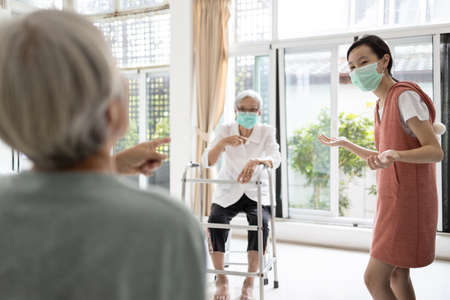 Family of elderly,senior woman,child girl are talking by maintain distancing,prevent infection of flu,Coronavirus,pandemic of Covid-19,people with prevention mask,maintain social distance for safety