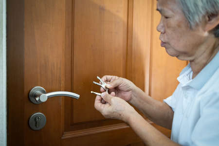 Asian senior woman is confused because she can not remember the key to opening the door of her bedroom,memory loss in elderly people,old patients with cognitive impairment,alzheimer,senile dementia