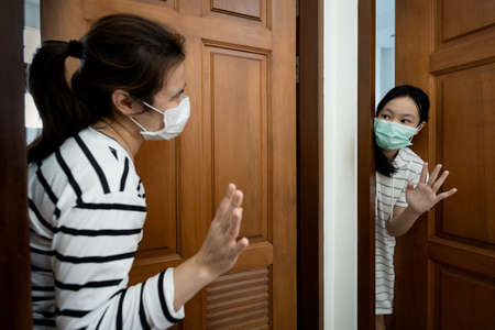 Mother and daughter standing at the door,greeting good night before going the bedroom,separate the room,self isolation quarantine,social distancing during the Covid-19 pandemic,Coronavirus,health care