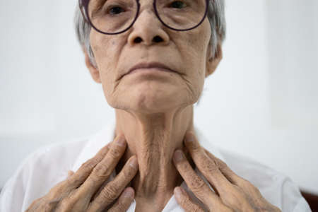 Close up of female neck,asian senior woman thyroid gland control,old elderly was touching the neck,checking thyroid gland with her hands,concept of thyroid disorder,sore throat,dysphagia,tonsillitis