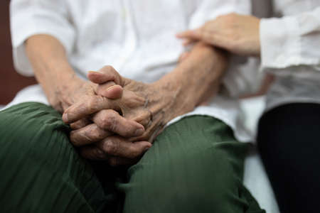 Old elderly patient hands clasped together because of excitement and nervousness,daughter holding touching her arm,care support encourage and empathy senior mother to be more confident at hospital