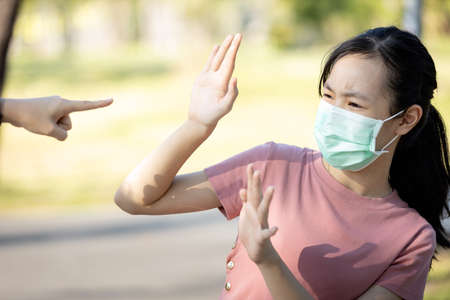 Problems of bullying at school,sad stressed asian girl student in medical mask,hand pointing finger to scared schoolgirl,bullying victim and hate,anti racism and stop xenophobia,bullied by society