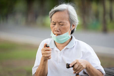 Asian senior woman hold a cigarette in her mouth,cigarette cravings,feeling stressful while wear a mask during the pandemic Covid-19,risk of Coronavirus infection,old elderly is addicted to smoking