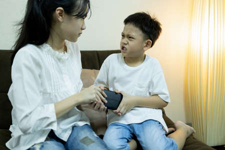 Asian sister and little brother fighting for smartphone,aggressive kid boy trying to grab a phone from child girl,two children quarreling, arguing for playing with phone,online game addiction problems