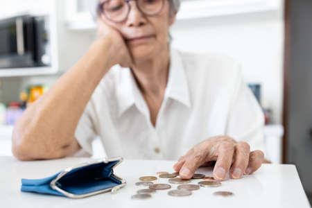 Stressed senior woman is counting remaining coins from pension,old elderly counting last money coins in her purse,financial problems,planning savings,no retirement savings,poverty, absence of money