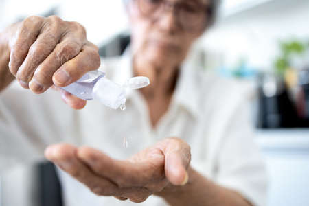 Asian senior woman is squeezing the hand sanitizer on her palm or pour lotion from bottle,cleaning,antibacterial,old elderly wash hand with alcohol antiseptic gel,disinfection of Covid-19,Coronavirus Zdjęcie Seryjne