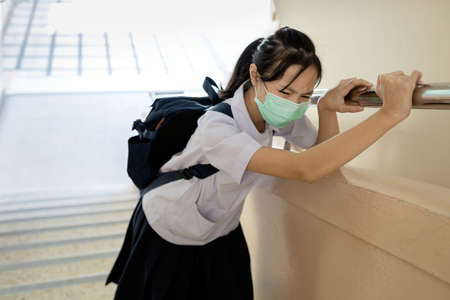 Student wearing a school uniform with a protective face mask,tired child girl have difficulty breathing