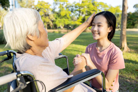 Happy asian senior grandmother is stroking her loving granddaughter head,support, care,old elderly and smiling child girl hand in hand with love,nostalgia while visiting her on weekend at nursing home