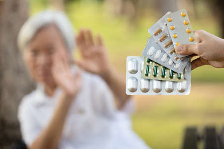 Hand of woman holding medicine tablets,capsules,show lots of  medication,old elderly on blurred background,senior people raise hand to refuse to take pills,afraid,fear and refuse to medical treatment