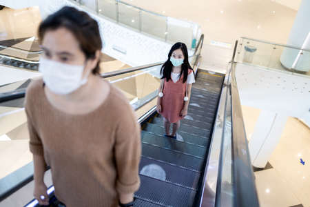 People,wearing protective face masks,using escalator by keep the distance at the white circles symbol on the escalator,safety,social distancing in shopping mall during its reopening,new normal life Zdjęcie Seryjne