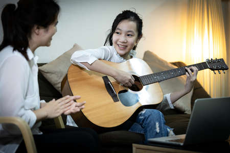 Happy asian child girl playing guitar,online learning,study music on laptop computer,daughter is showing the guitar to her mother, singing a song together having fun,enjoying while practicing at home