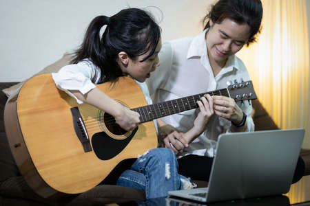 Asian woman teaching child girl to play guitar, student learning how to play the guitar with the help of a teacher, happy daughter is playing guitar study music and practicing from her mother at home Zdjęcie Seryjne