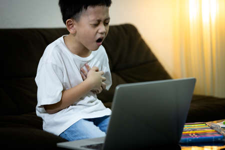 Sick asian kid boy with chest pain suffering from heart attack,ill little child male having dyspnea,shortness of breath or congenital heart disease while studying online at home,health care concept Zdjęcie Seryjne