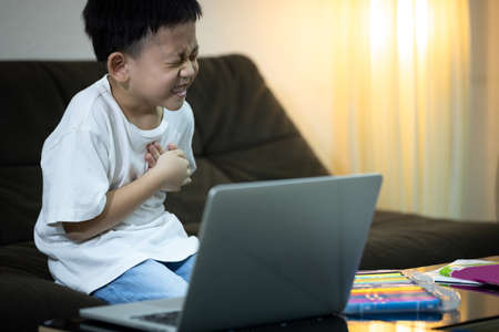 Asian kid boy with chest pain suffering from heart attack,little child male having difficulty breathing,painful,symptoms of heart problems or congenital heart disease while studying online at home Zdjęcie Seryjne